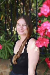 Instructor and co-founder Jackie Bryant, a Caucasian women with long flowing brown hair standing in a tropical garden