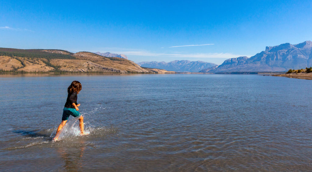 A young girl running in a lake with Canadian Rocky Mountains in the distance