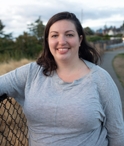 Instructor and cofounder Naomi Tomky, a Caucasian woman in a grey shirt, smiling as she leans against a fence in the Pacific Northwest. A curving trail and evergreen trees are visible in the background