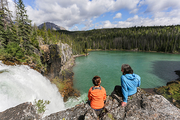 Two women sitting at the edge of a Canadian Rockies cliff in Tumbler Ridge, BC, right beside a waterfall dropping into a blue-green alpine lake