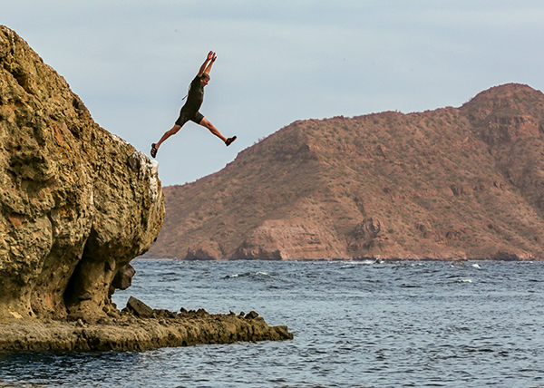 A dude in a tropical shortie wetsuit jumping off a sea cliff in Baja, Mexico, with ruddy mountains in the background