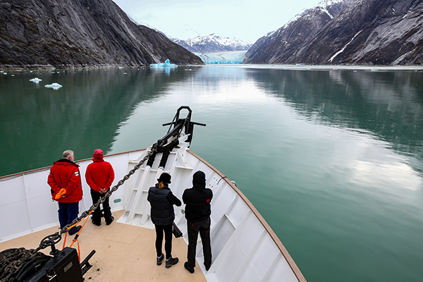 Passengers on the deck of an Uncruise vessel, staring at the blue-green Dawes Glacier in Alaska in the background