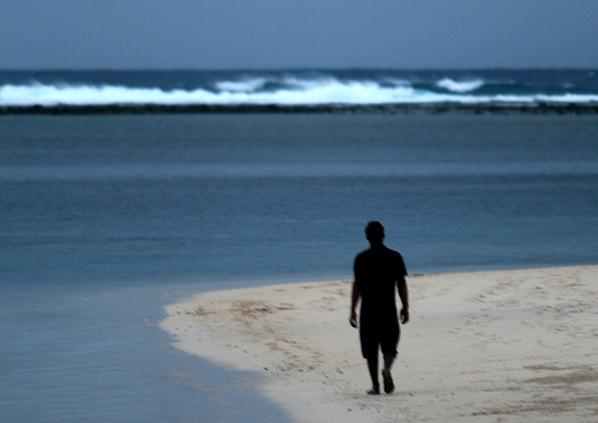 The silhouette of a man walking down a tropical white beach in the Cook Islands, facing a story sea and reef break