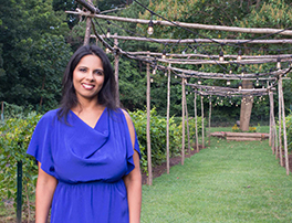 A smiling Indian-American author, wearing an elegant purple dress, against a garden backdrop with a trellis of lights