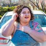 Chaya Milchtein, an automotive writer and plus size model sits on the trunk of a white car on a sunny day. She is tucking her dark curls behind one ear and a colorful tattoo sleeve peeks out from under her overalls. She looks playful and welcoming.