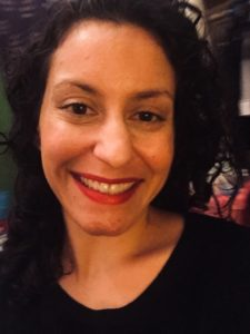 A close-up of a Latinx woman with dark hair, a wide smile and red lipstick. She's wearing a black v-necked shirt.