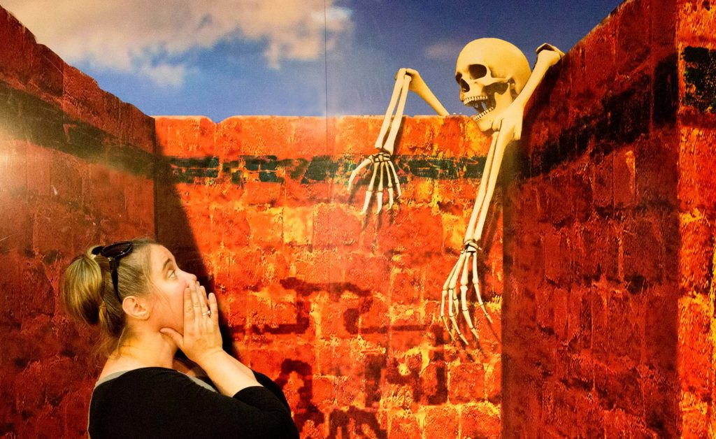 A white woman with a brown bun mock-screaming in horror at a skeleton climbing over a bright-red brick wall (an exhibit in Moji Japan's 3D museum)