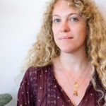 Writer Flora Tsapovsky from Tel Aviv, a white woman with long, curly blonde hair, a V-neck maroon blouse and a delicate necklace