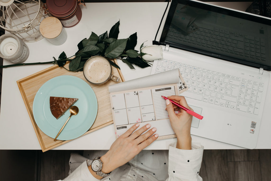 Overview of a chic business woman's desk, including a laptop, calendar and PIE! The color palette is pale and dreamy.