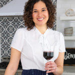 Food writing instructor Kae Lani Palmisano, a smiling biracial woman with dark shoulder-length curls. She's posed in a chic kitchen, holding a glass of red wine and wearing a white, short-sleeved blouse with a pussycat bow.