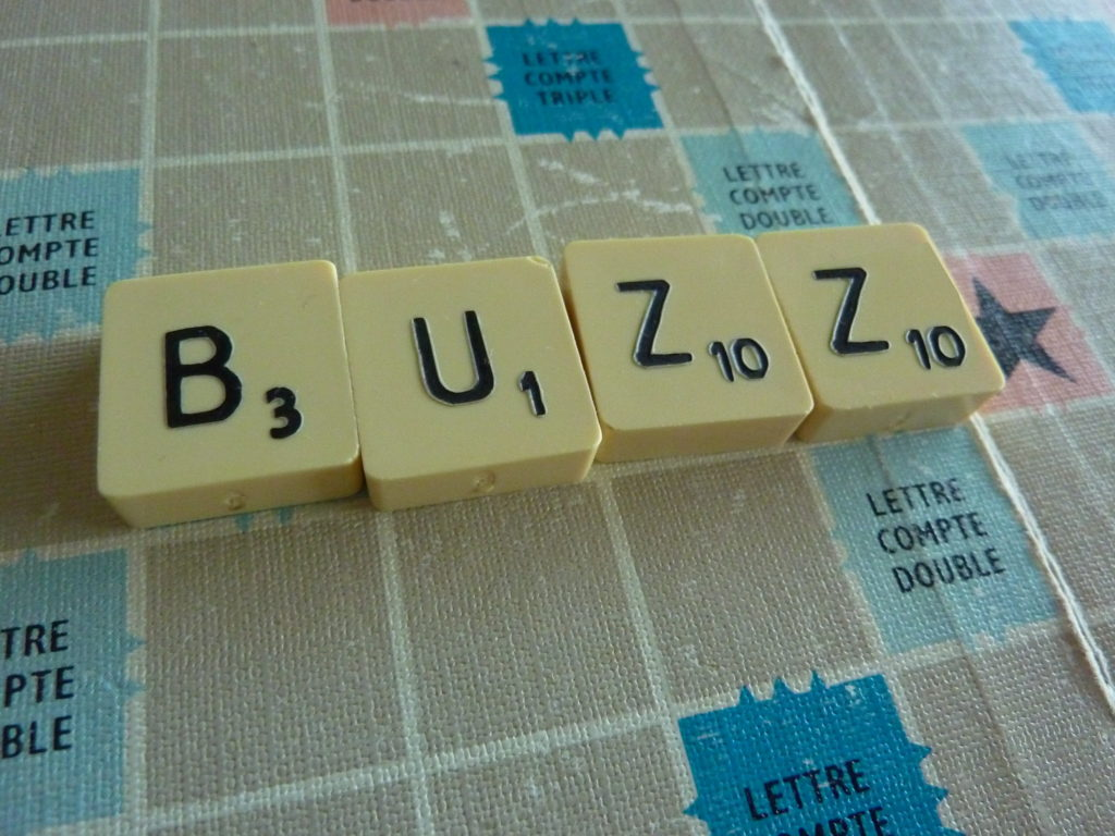 """Scrabble tiles spelling out """"buzz,"""" placed on a Scrabble board."""